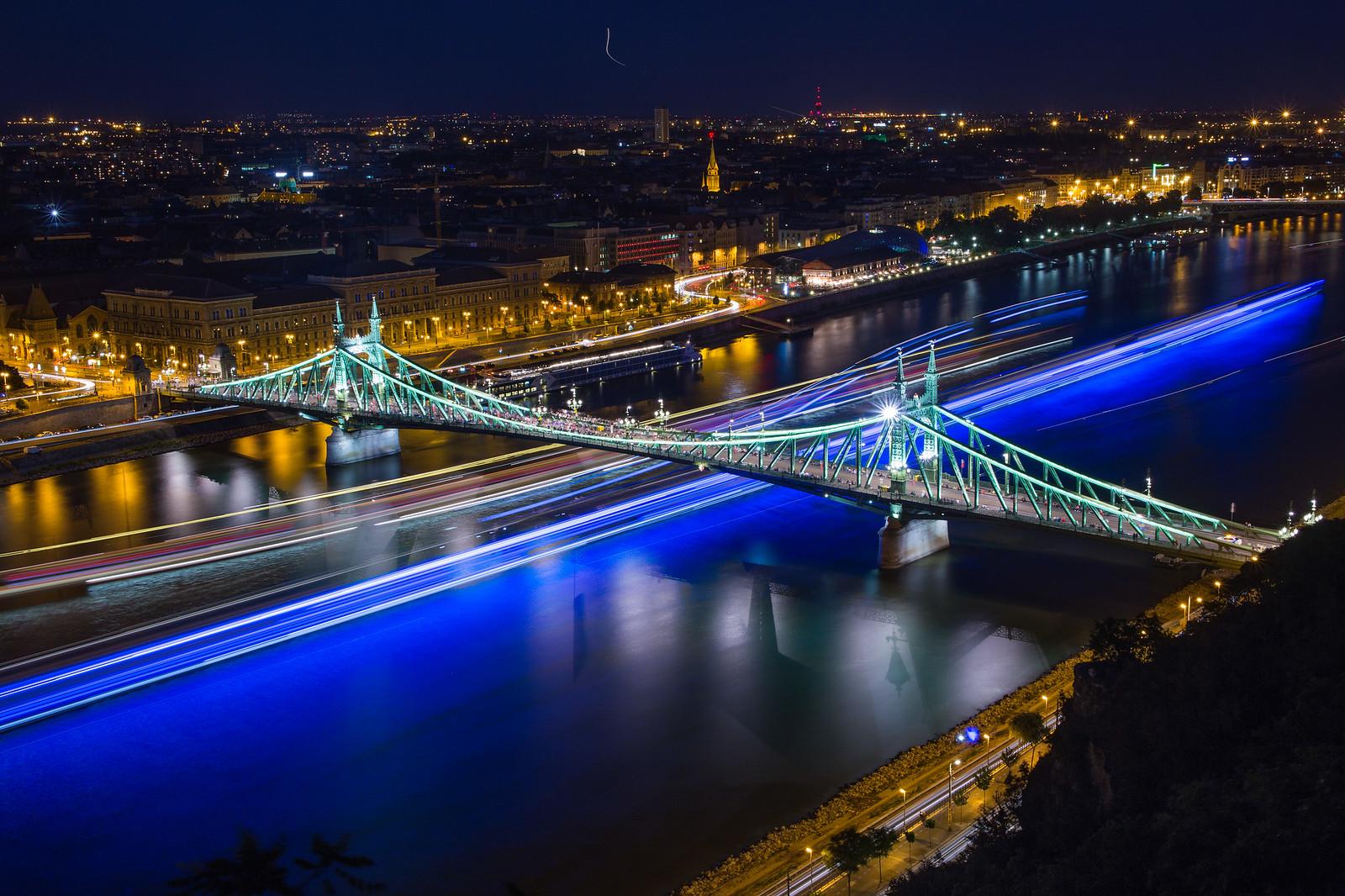 Hajók kék fénycsíkjai és a Szabadság híd a Gellért hegyről